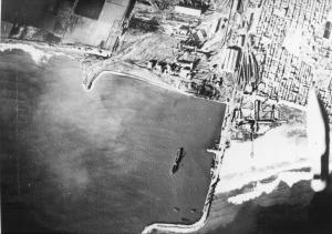 Fotografía del Puerto de Sagunto del bombardeo italiano del 19 de diciembre de 1937 en el que se puede apreciar a la derecha de la imágen la silueta de una bomba de 100 kg cayendo desde la bodega de carga (Archivo Ángelo Emiliani)